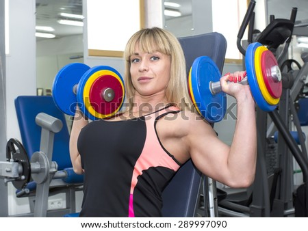 young girl engaged in bodybuilding in the gym