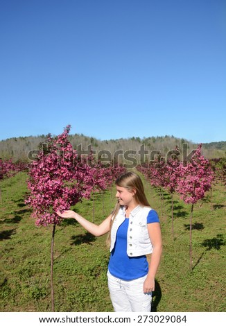 Young girl enjoying beauty of  blooming trees. - stock photo