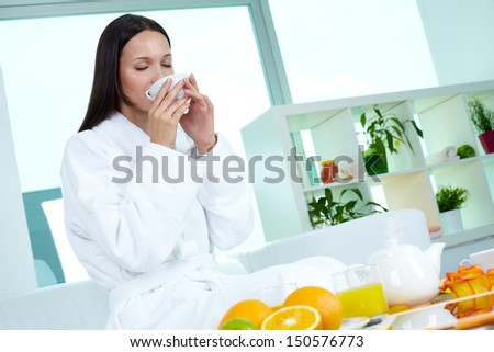 Young girl enjoying herbal drink in spa salon