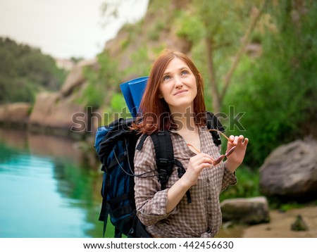 Young girl enjoying nature on backpacking trip in the mountains. - stock photo