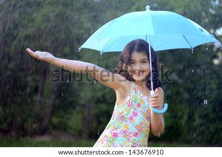 young girl enjoying the rain - stock photo