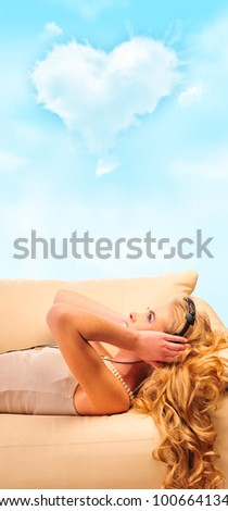 Young Girl enjoys listening music in headphones lying on sofa and daydreaming about love. Cloud of heart shape overhead - stock photo