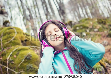 Young girl enjoys listening to music with headphones in nature - vintage look - stock photo