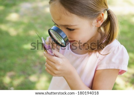 Young girl examining a butterfly with magnifying glass at the park - stock photo