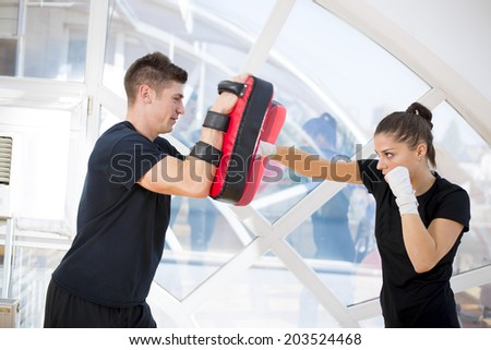 Young girl exercise punching with her coach - stock photo