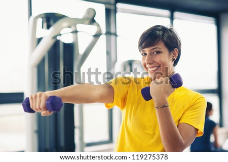 Young girl exercising with dumbbells in the gym. - stock photo