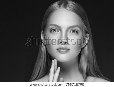 Young girl face beauty skin portrait with long blonde hair with hand over dark background. Studio shot.