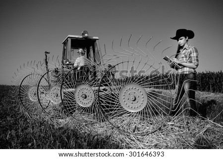 Young girl farmer standing beside haying rake attached to tractor, black and white image