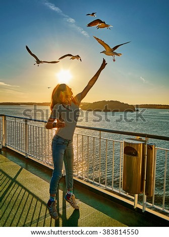 Young girl feeding seagulls in the flare of setting sun onboard a ferry - stock photo