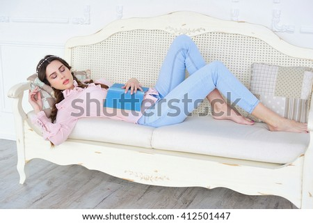 Young girl fell asleep while reading on a sofa
