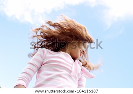 Young girl flicking her hair in the air against a blue sky.