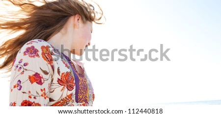Young girl flicking her hair on a golden sand beach with the sun rays filtering through her hair while she smiles, joyful. - stock photo