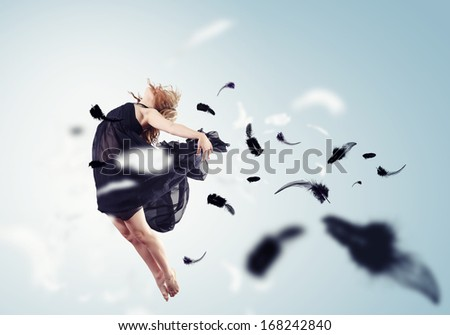 Young girl flying among the feathers like a bird