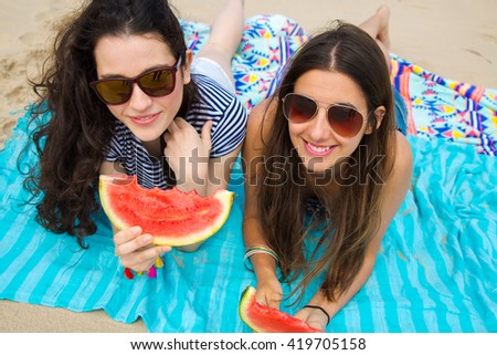 Young girl friends on the beach eating watermelon - stock photo