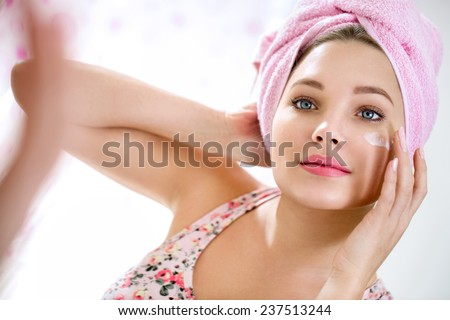 Young girl front of mirror in bathroom putting cream on her face - stock photo