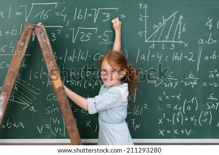 Young girl genius in maths class using a stepladder to reach the complex equations on the blackboard turning to grin at the camera - stock photo