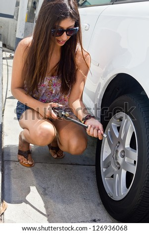 Young girl gets ready to add air to the car tire. - stock photo