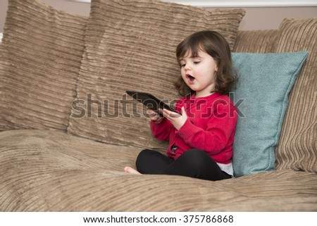 Young girl getting into learning on her tablet - stock photo