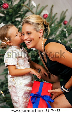 Young girl gives a gift to her mother, kissing her - stock photo