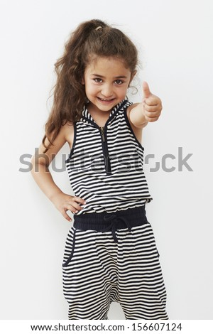 Young girl giving thumbs up against white background