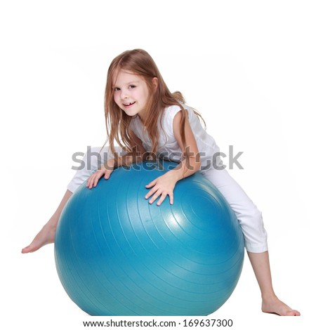 Young girl goes in for sports on fitball and smiling isolated on white - stock photo
