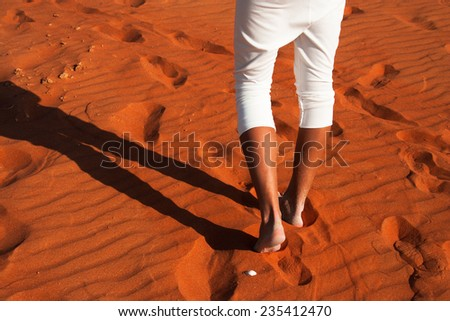 Young girl got lost in the desert. Focus on her legs in a white. grain added - stock photo