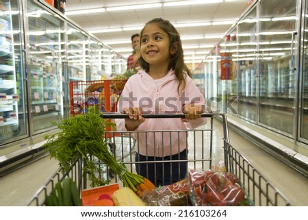 Young girl grocery shopping in frozen foods section - stock photo