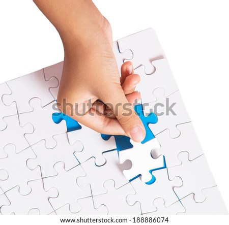 Young girl hand putting jigsaw puzzle pieces together
