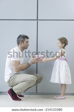 Young girl handing present to her father - stock photo