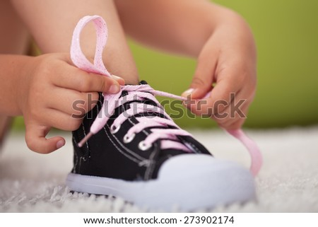 Young girl hands tie shoe laces - closeup - stock photo