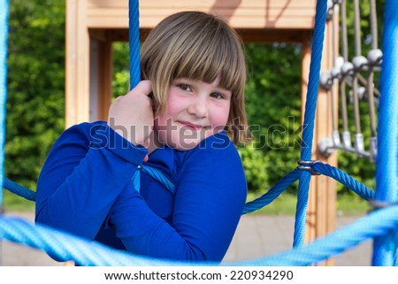 Young girl hanging on blue ropes - stock photo