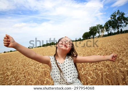 Young girl have fun in the wheat field - stock photo