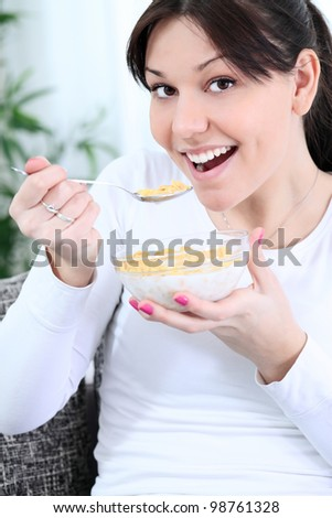 Young girl having a healthy breakfast - cornflakes with fresh fruit - stock photo