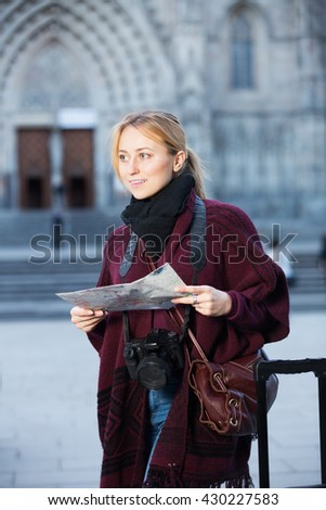 Young girl having a map and looking for her route in the city
