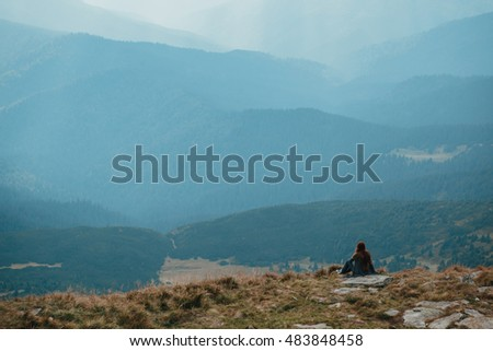 Young girl having a rest at the top of the mountain. Calm concept. Meditation. Nature loving