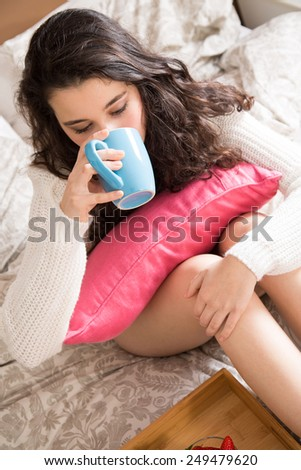 Young girl having breakfast in bed - stock photo