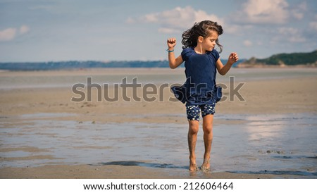 Young girl having fun on the beach in front of Mont Saint Michel ancient village. Normandy, France. - stock photo