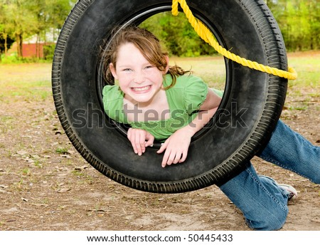 Young girl having fun on tire swing - stock photo
