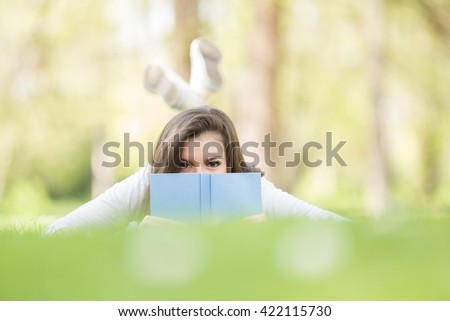 Young girl having fun while reading book on grass. - stock photo