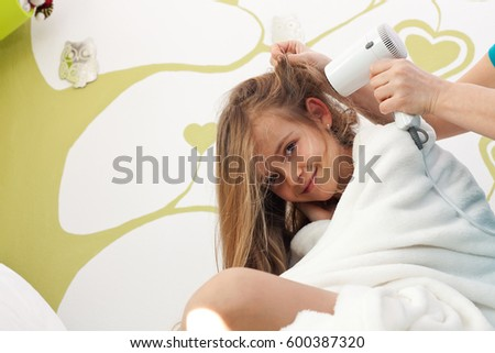 Young girl having her hair dried after bath - sitting in bed enjoying her beauty ritual