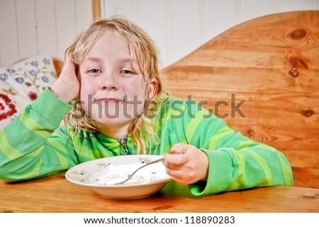 Young girl having snack at the table.