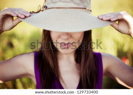 Young girl hidden under her hat. Focus on lips. - stock photo