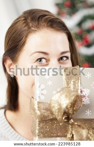 young girl hide behind christmas present box - stock photo