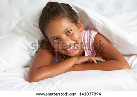 Young Girl Hiding Under Duvet In Bed - stock photo