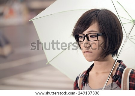 Young girl hold umbrella and stand at street in Taipei, Taiwan. - stock photo