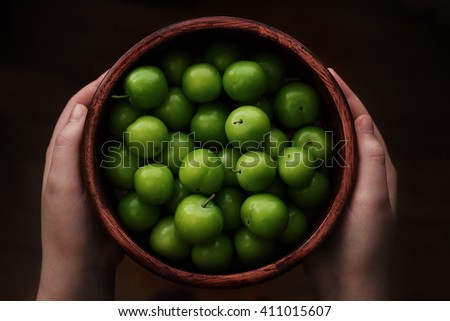 Young girl holding a bowl of green plums. Food, healthy eating and lifestyle concept