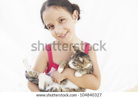 Young girl holding a kitten in her arms and smiling at camera.