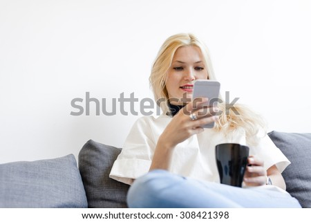 Young girl holding a mug while typing on mobile phone - stock photo