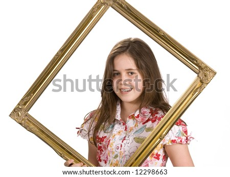 Young girl holding a picture frame around her face