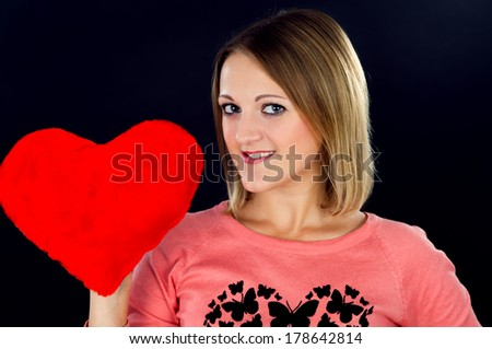 Young girl holding a red heart - stock photo